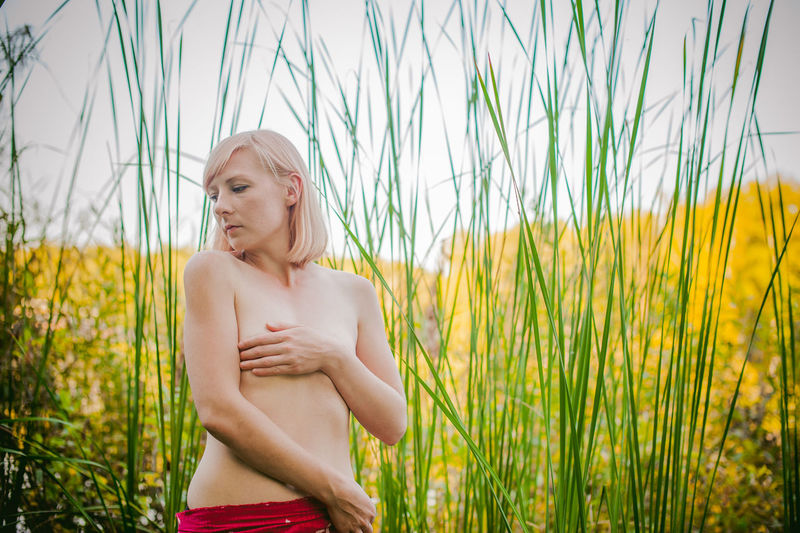 Shirtless Seductive Woman Standing On Field Against Sky