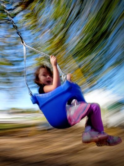 Blurred motion of girl sitting on swing in playground