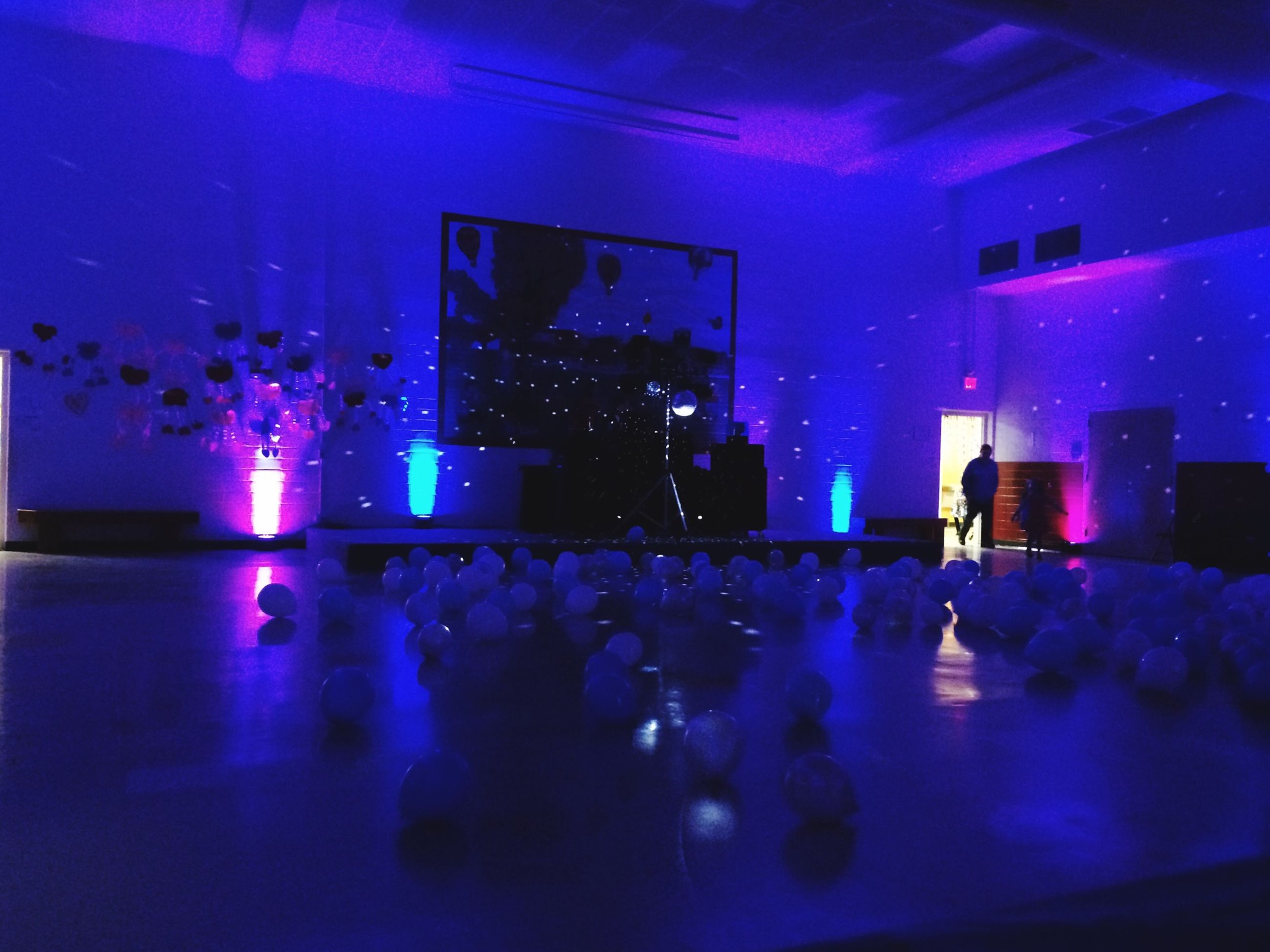 indoors, illuminated, large group of people, men, lifestyles, crowd, night, nightlife, person, leisure activity, arts culture and entertainment, music, enjoyment, concert, blue, stage - performance space, light - natural phenomenon, lighting equipment