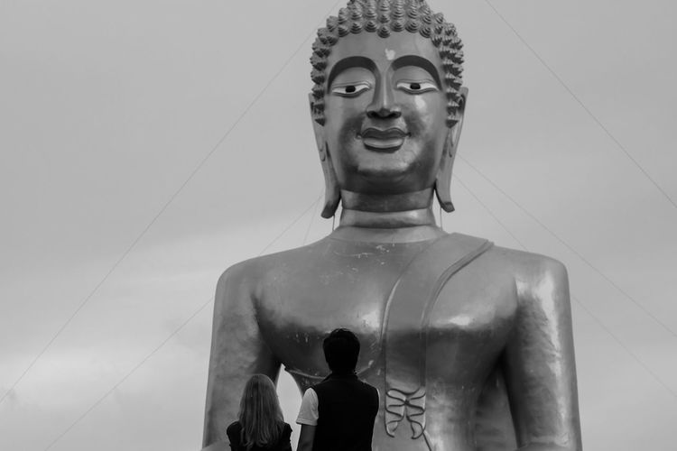 Rear view of couple standing against buddha statue against sky