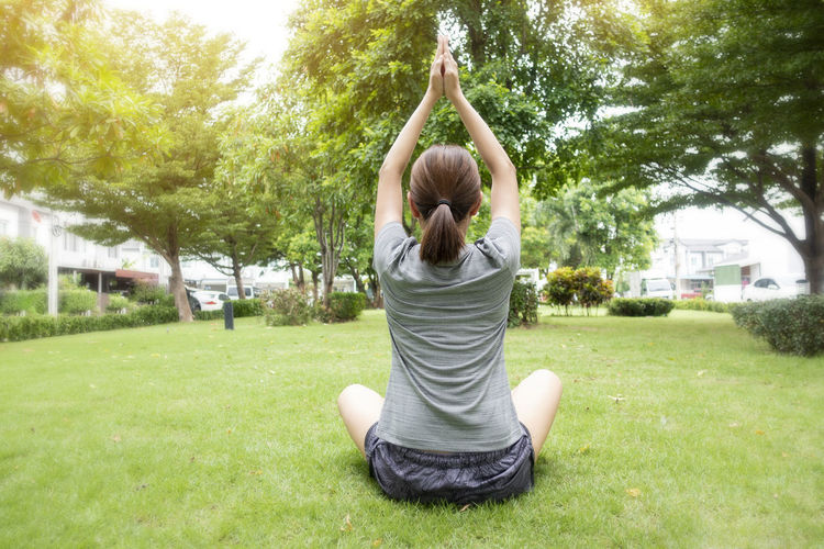 Rear view of woman practicing yoga at park
