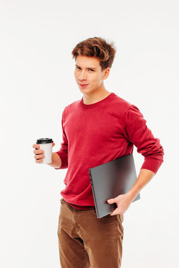 Young man drinking coffee cup against white background