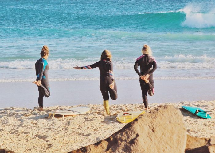 Rear View Of Surfers Exercising On Sand At Beach