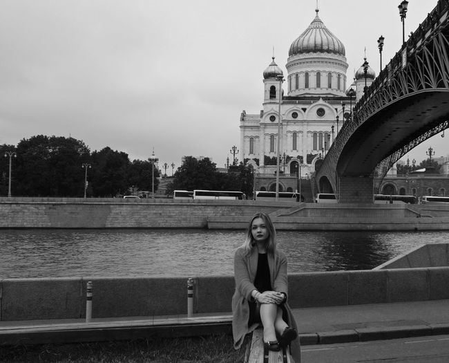 Portrait of woman sitting by bridge over river against church and sky