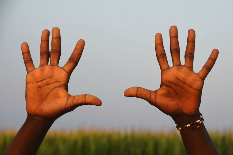 Cropped hands of person showing stop gesture against sky