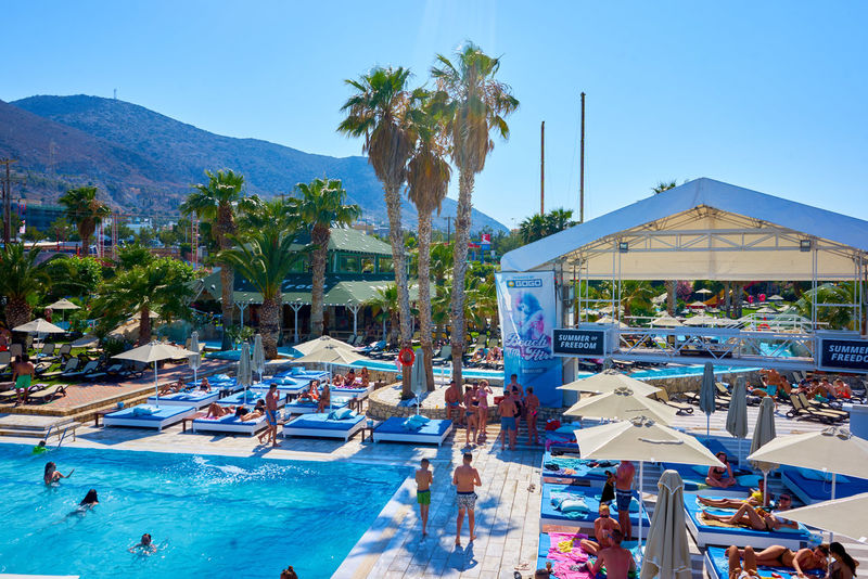 Chersonissos Holiday Resort Starbeach Architecture Beachclub Blue Built Structure Day Group Of People Incidental People Mountain Nature Outdoors Palm Tree Parasol Plant Pool Sky Sunbeds Sunlight Swimming Pool Tourist Resort Tree Tropical Climate Water