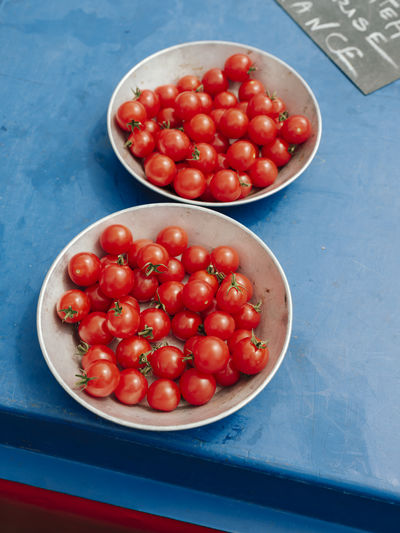 High angle view of cherry tomatoes in bowls on table