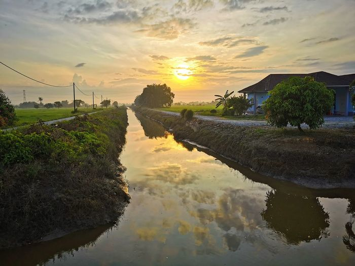 Scenic view of canal against sky during sunset