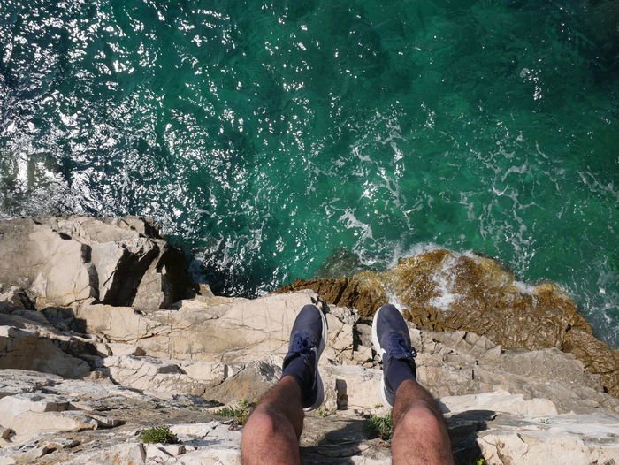 Low section of man on rock by sea