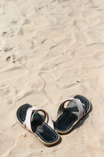 High angle view of slippers on sand at beach