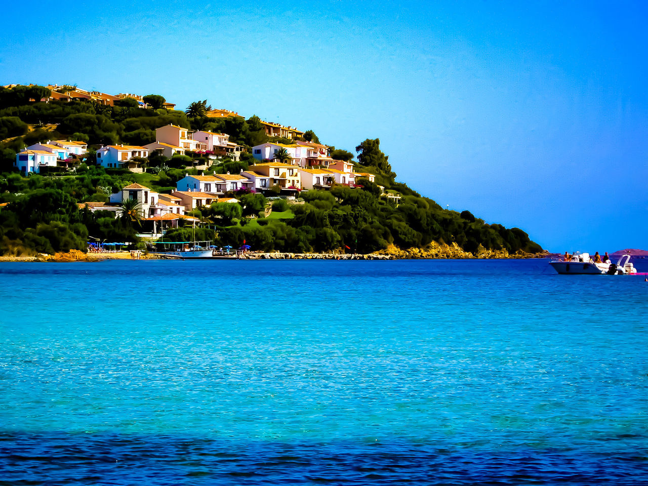 blue, water, building exterior, sea, built structure, architecture, house, waterfront, mountain, nature, scenics, beauty in nature, outdoors, residential building, clear sky, day, rippled, tranquility, tourist resort, town, sky, tree, no people, view into land, travel destinations, nautical vessel