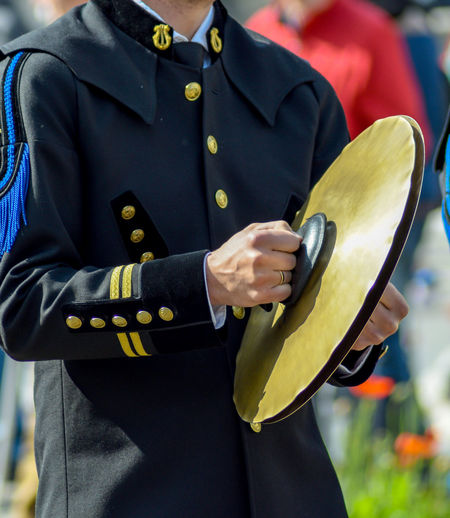Midsection of man holding cymbals