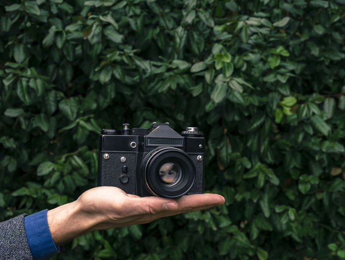 Male hand holding a vintage film camera in the air. Green nature in the background. Camera Camera - Photographic Equipment Film Plant Retro Analog Backgrounds Black Equipment Green Background Hand Holding Leaves Lens Old Outdoors Vintage Zenit