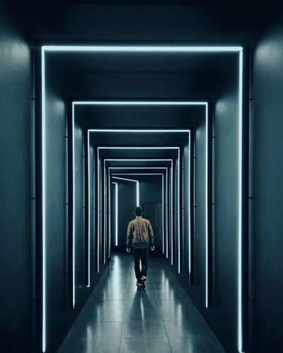 Rear view of man walking in illuminated corridor