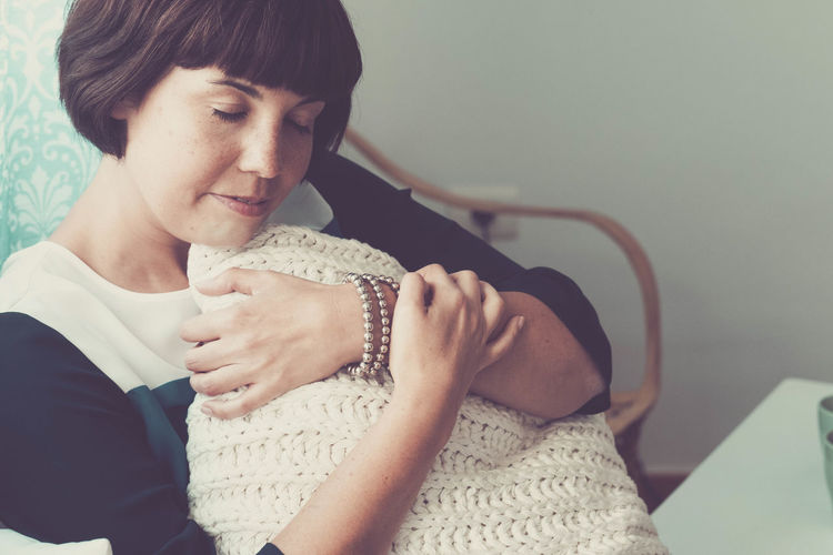 Sweet young woman hug with love and protection a white cover at home - tenderness emotions and dreaming concept for female with closed eyes Real People Lifestyles Young Adult One Person Indoors  Sitting Women Front View Leisure Activity Casual Clothing Adult Young Women Three Quarter Length Focus On Foreground Looking Home Interior Clothing Seat Hairstyle Contemplation One Woman Only Embracing Short Hair Brunette Home Thinking Bracelet Closed Eyes Relaxing Relaxation Dreaming Sweet Females Portrait Pretty Domestic Life