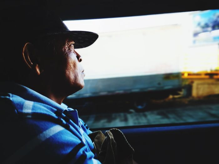 Man looking through window while sitting in vehicle