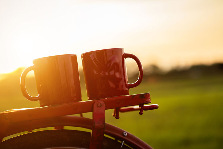 Close-up of coffee cup against orange sky