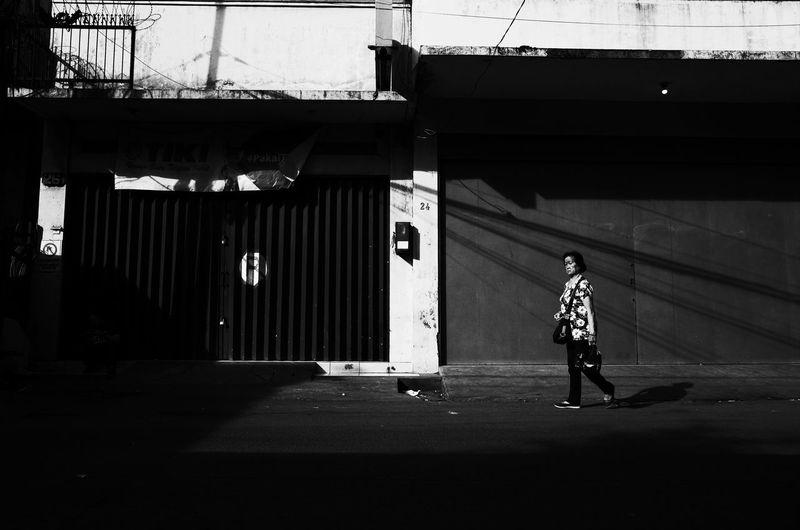 Full length of woman walking on illuminated road