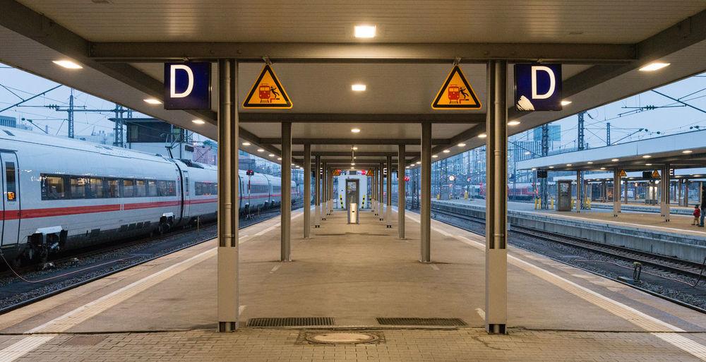 People at railroad station platform against sky