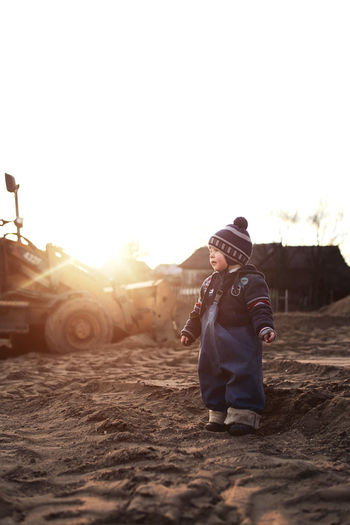 Full length of baby boy standing on land against clear sky during sunset