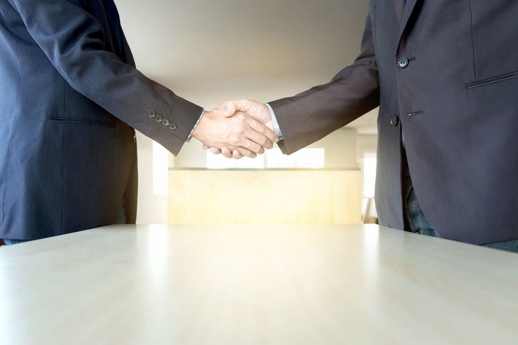 Midsection Of Businessmen Shaking Hands At Office