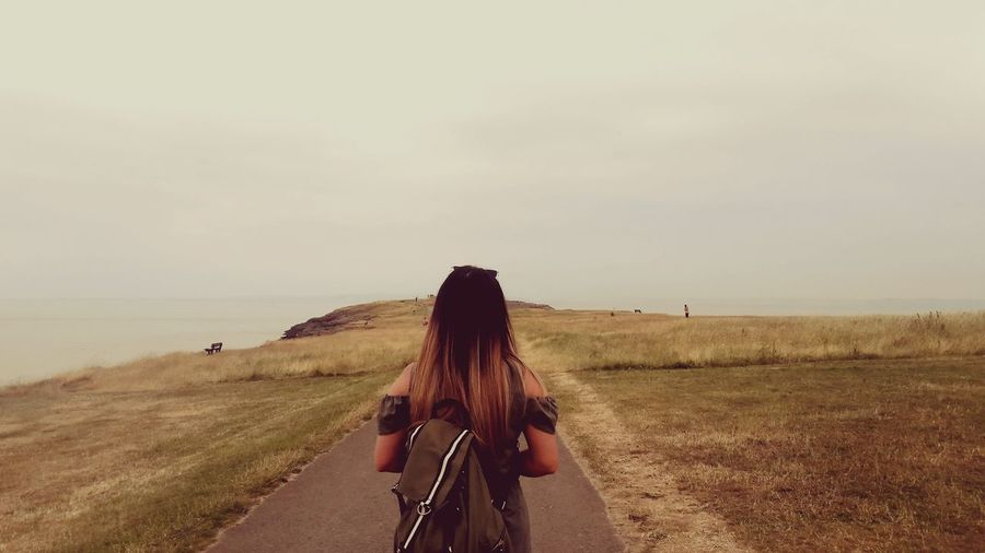 Rear view of woman with backpack standing on road against sky