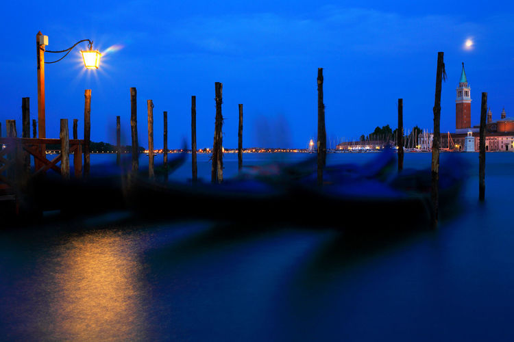 Boats moored on grand canal by illuminated street light against blue sky at night