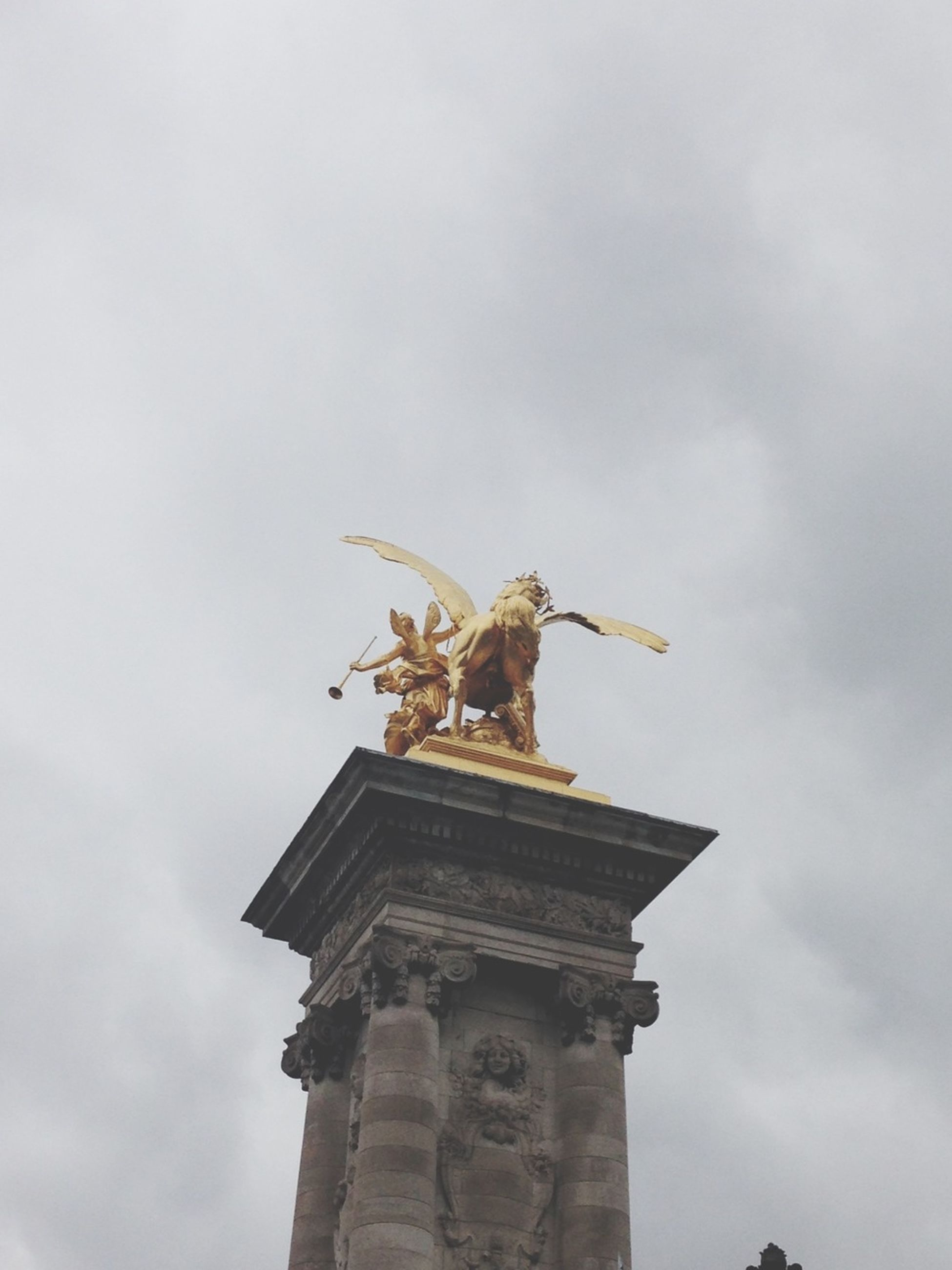 low angle view, sky, statue, sculpture, architecture, built structure, human representation, art and craft, art, animal themes, cloud - sky, animals in the wild, history, one animal, animal representation, building exterior, outdoors, creativity, day, no people