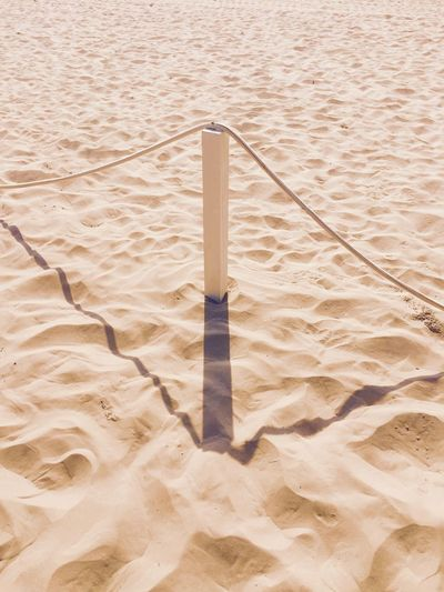 Wooden bollard on the beach Light Background Beach Bollard Close-up Day High Angle View Light And Shadow Minimal No People Outdoors Sand Sand Dune Shadow