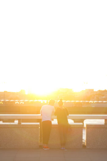 Rear view of young couple standing on bridge during sunset