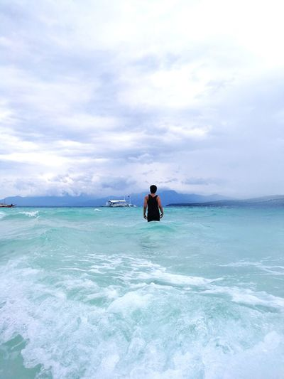 Rear View Of Man Standing In Sea Against Cloudy Sky