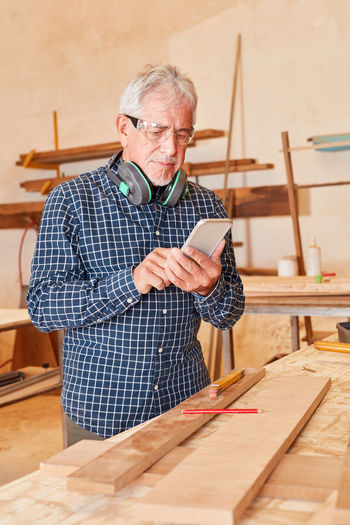 Senior carpenter using mobile phone at workshop