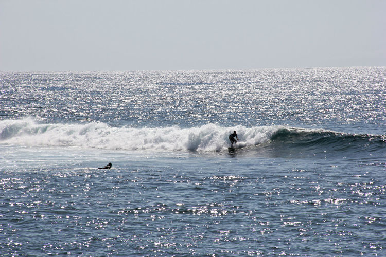 Man surfboarding in sea against clear sky