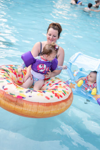 Mother holding daughters sitting on inflatable ring in swimming pool