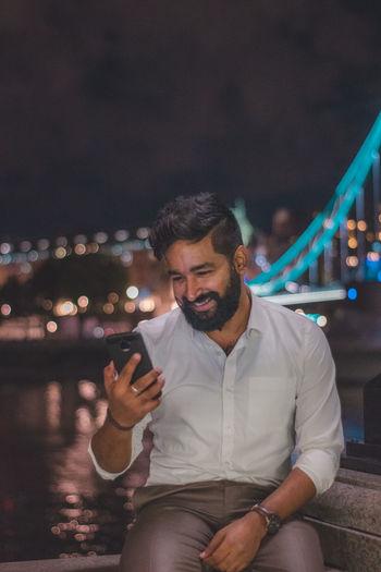 Young man looking at camera while standing at night