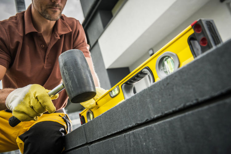 Midsection of man working on yellow cart