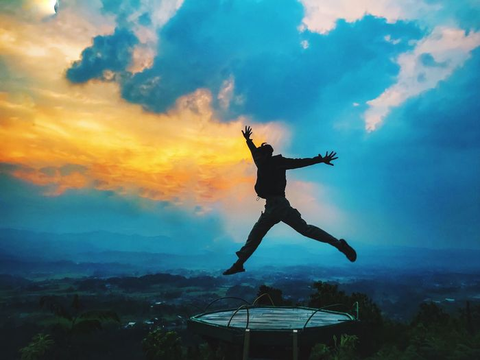 Silhouette man jumping over land against sky during sunset