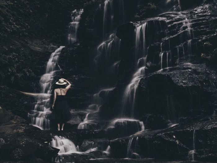 Rear view of woman standing against waterfall in forest
