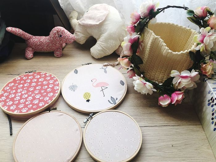 High angle view of embroidery frames by basket and stuffed toys on floor