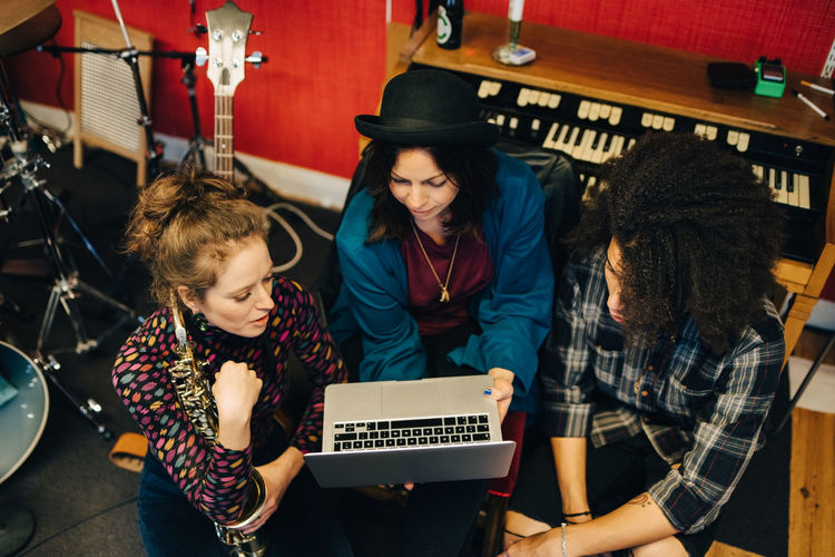 Male and female friends with various instruments looking at laptop at recording studio