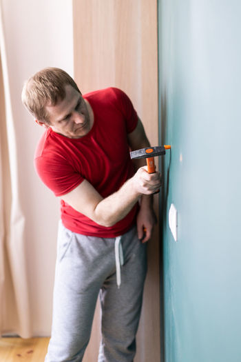 Full length of man standing against wall at home