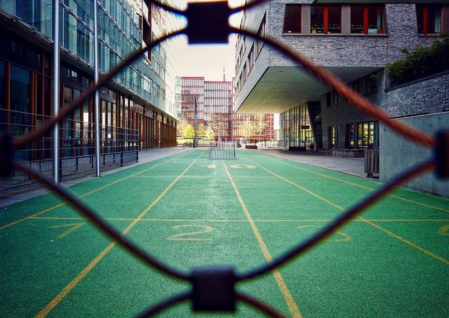 Sportpark in the City Citysport Gated Community Sport Area Built Structure Architecture Building Exterior Fence Sport Day Chainlink Fence Metal No People Focus On Background Nature Building Outdoors Barrier Boundary Security Diminishing Perspective Railing Protection Grass The Street Photographer - 2018 EyeEm Awards