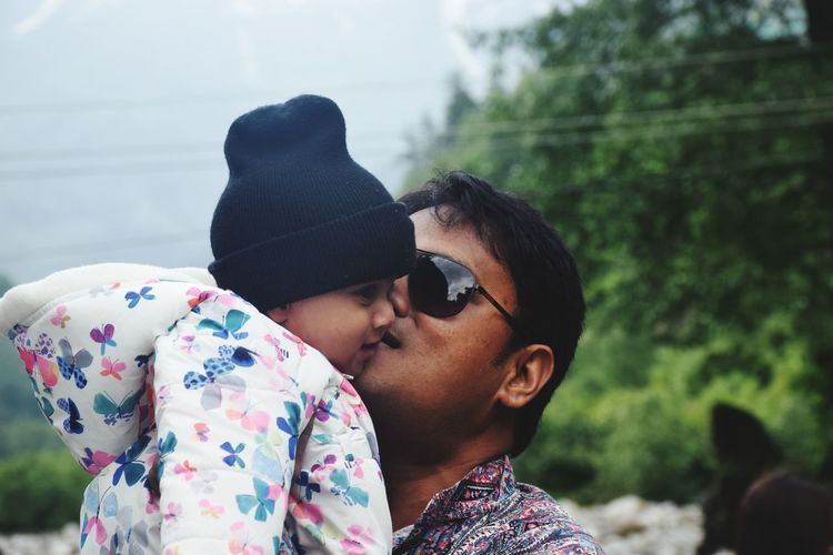 Close-up of father kissing baby outdoors