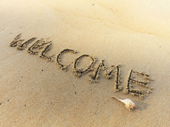 welcome wording writing on the sea sand and a seashell at the end of the word Beach Day Handwriting  Nature No People Outdoors Sand Seashell Sunrise Text Welcome