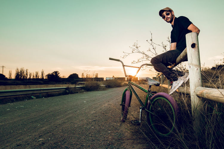 Side View Portrait Of Man Sitting With Bicycle On Road During Sunset