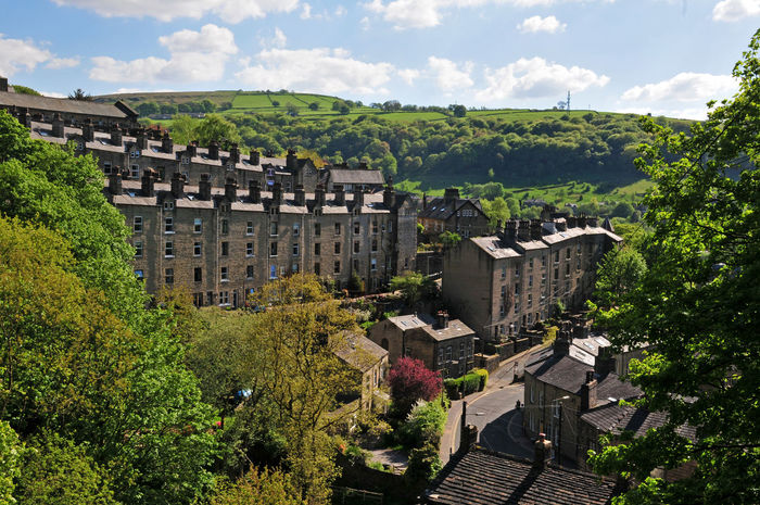 houses between trees in hebden bridge west yorkshire Hebden Bridge Architecture Building Building Exterior Built Structure Cloud - Sky Day Green Color Growth High Angle View History House Nature No People Outdoors Pennines Plant Residential District Sky Town Tree Valley