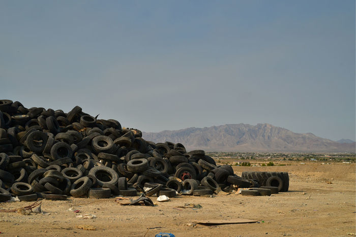 worn-out vehicle tires stacked and piled in the Mojave Desert with mountains in distant landscape in the town of Pahrump, Nevada, USA Junk Tires Abundance Copy Space Day Desert Junk Environment Land Landfill Landscape Large Group Of Objects Mountain Nature Nevada No People Outdoors Pahrump Recycle Reuse Rubber Sky Stack Tire Wheel Worn Out