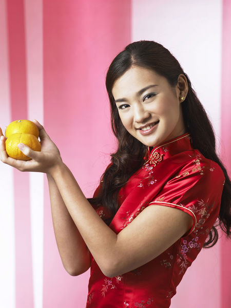 chinese woman holding pair of mandarin oranges greeting Gong Xi Fa Cai Greeting Happiness Mandarin Oranges Beautiful Woman Cheerful Cheongsam Chinese Ethnicity Chinese New Year Holding Lifestyles Looking At Camera Orange - Fruit People Portrait Qipao Side View Smile Smiling Standing Waist Up Young Adult Young Women