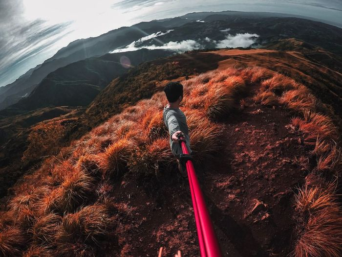 Side view of man holding monopod while standing on mountain
