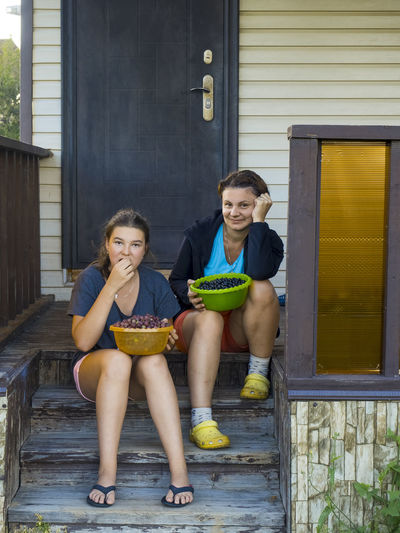 Portrait of mother and daughter sitting at porch